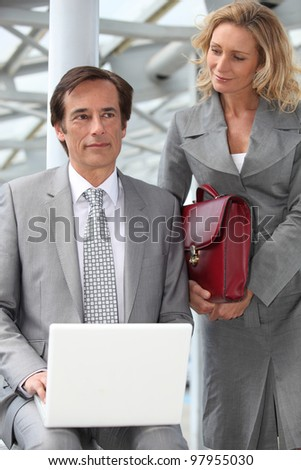 Man using a laptop computer accompanied by a woman with a red briefcase - stock photo