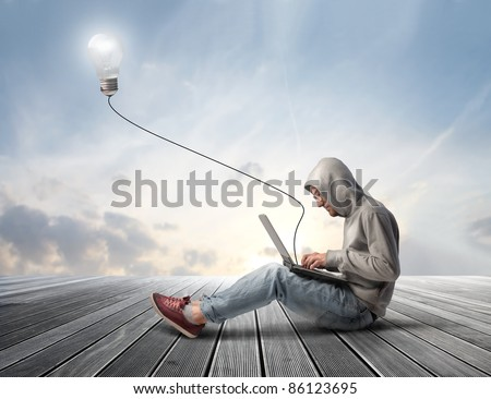 Man using a laptop with light bulb plugged in it