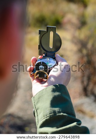 Man using a magnetic compass to navigate in the wilderness and find his location, close up of his hand - stock photo