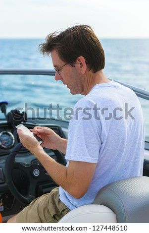 Man using a smart phone while boating. - stock photo