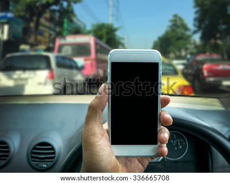 man using a smart phone while driving a car - stock photo