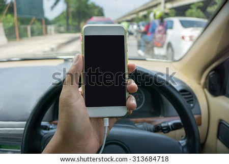 man using a smartphone while driving a car - stock photo