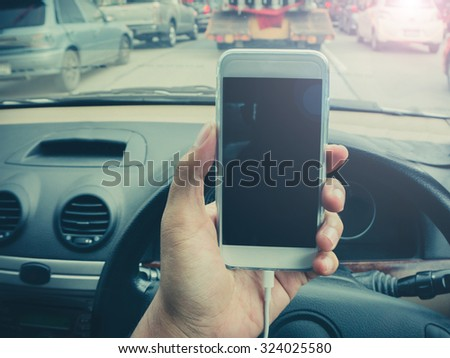 man using a smartphone while driving a car with a filter effect - stock photo