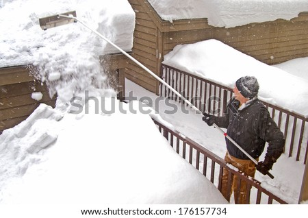 man using a snow rake on garage roof in winter - stock photo