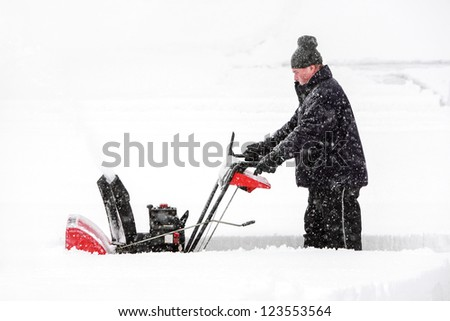 Man using a snowblower - stock photo