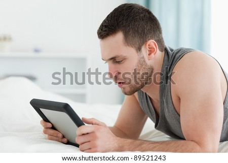 Man using a tablet computer while lying on his belly in his bedroom - stock photo