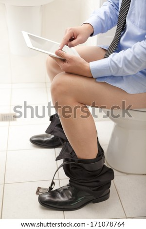 man using a tablet PC while sitting on the toilet. - stock photo
