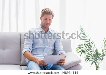 Man using a tablet while he is sat on the couch in the living room - stock photo