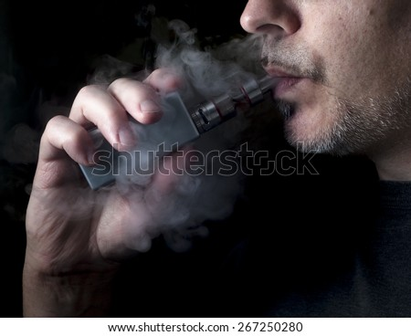 Man using an advanced personal vaporizer or e-cigarette, close up; low-key image. - stock photo