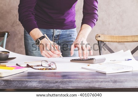 Man using calculator and writing on large whatman in office - stock photo