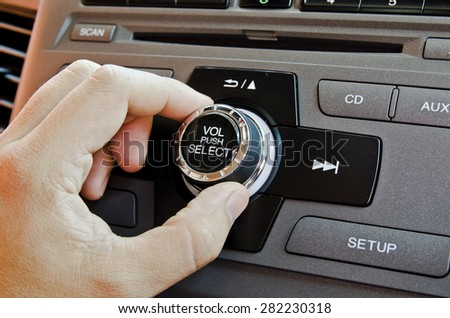 Man using car volume audio control. - stock photo