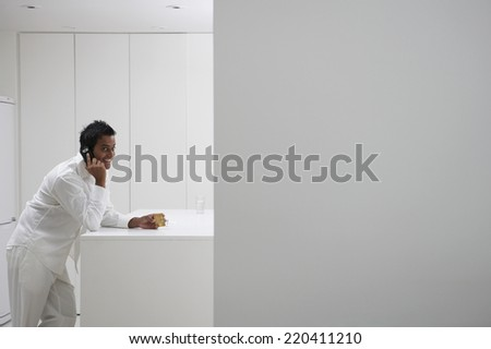 Man using cell phone in kitchen - stock photo