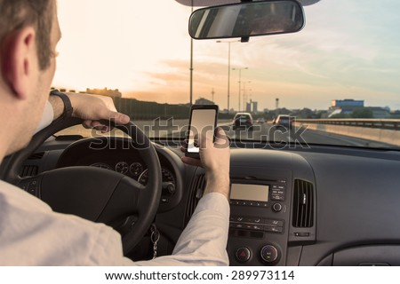 Man using cell phone while driving - stock photo