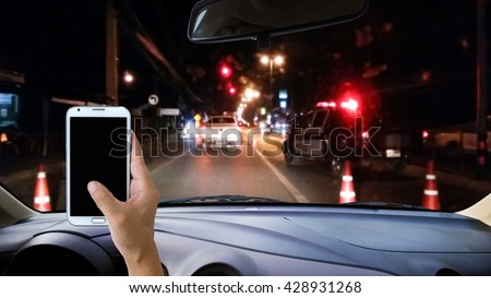 Man using cell phone while driving, blur image of police checkpoint at dark night as background. - stock photo