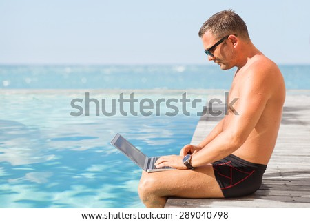 Man using computer by the pool - stock photo
