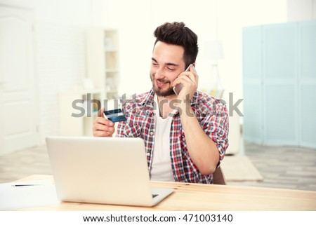 Man using credit card, phone and laptop for online shopping