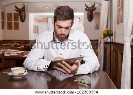 Man Using Digital Tablet At Cafe - stock photo