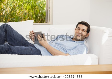 Man using digital tablet on couch