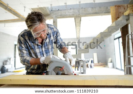 Man using electric saw inside house under construction - stock photo