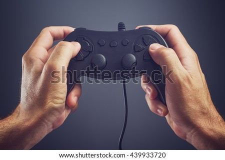 Man using game pad controller to play entertaining electronics video games, gaming and entertainment concept - stock photo