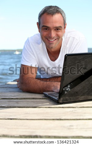 Man using his laptop on a wooden jetty - stock photo