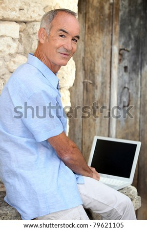 Man using his laptop outside - stock photo