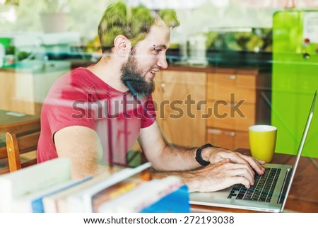 man using his laptop - view through the window