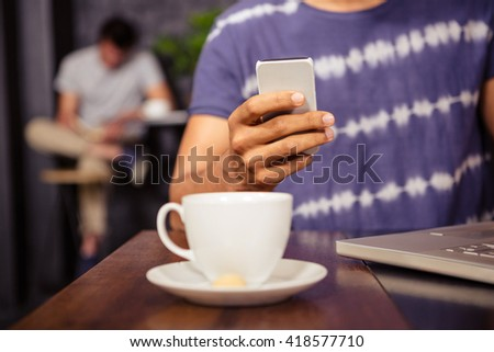 Man using his smartphone in a coffee shop - stock photo