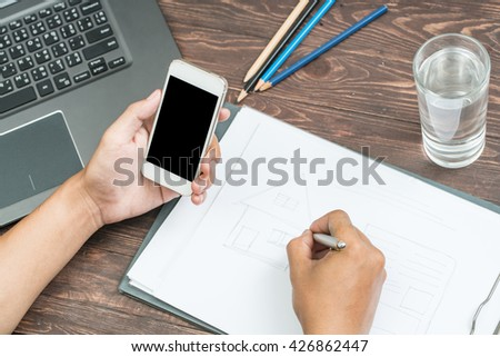 Man using his tablet with left hand and writing notes with right hand in personal notebook.