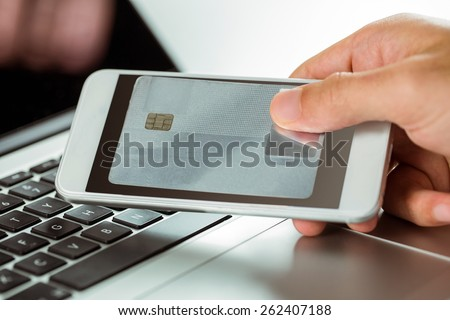Man using laptop and phone for online shopping in close up - stock photo