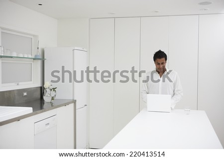 Man using laptop on counter in kitchen - stock photo