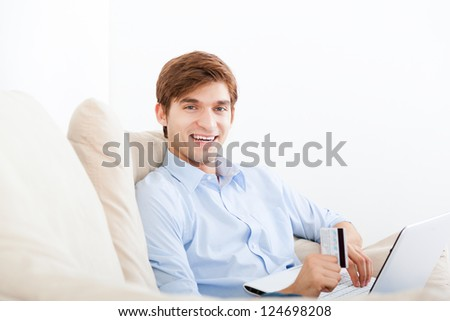 man using laptop shopping on line sitting on a sofa happy smile, hold credit card, young handsome guy smile relaxing on couch at home - stock photo