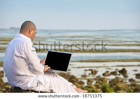 man using laptop while having his holiday - stock photo