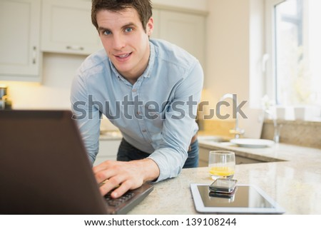 Man using laptop with smartphone and tablet in kitchen - stock photo