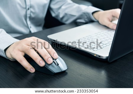 Man using laptop with white keyboard. Working in office - stock photo