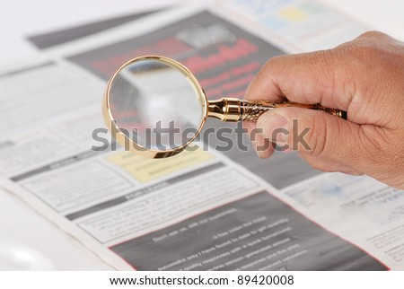 man using magnify looking for jobs - stock photo