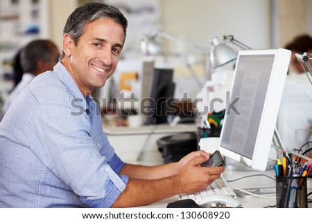Man Using Mobile Phone At Desk In Busy Creative Office - stock photo
