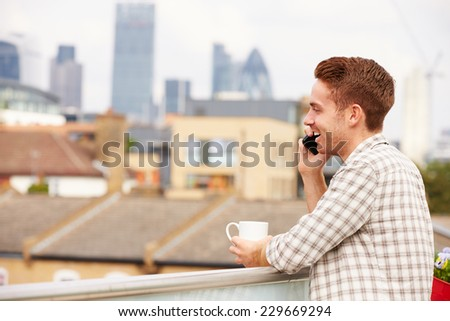 Man Using Mobile Phone On Rooftop Garden Drinking Coffee - stock photo