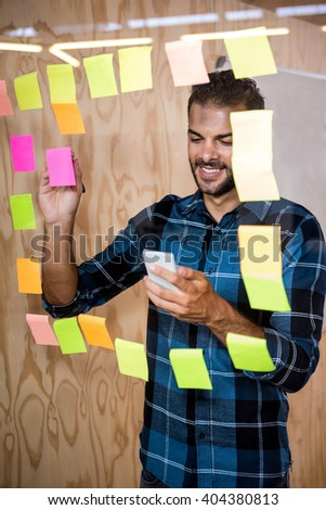 Man using mobile phone while writing on sticky notes in office