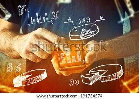 man using mobile phone with drawings of charts and other infographics in note pad. Close up image with selective focus. Business situation. - stock photo