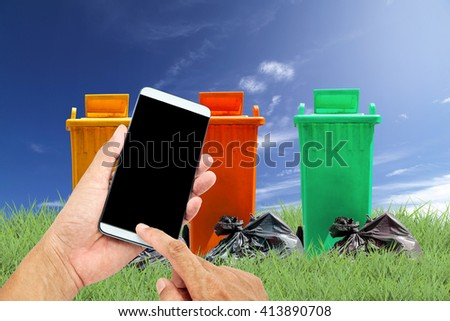 man using mobile smart phone control with recycle bins and bag garbage on green grass  background ,ecology concept - stock photo