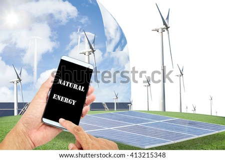 man using mobile smart phone control with Solar panels,wind turbines on green grass with blue sky background,natural Energy concept - stock photo