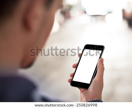 Man using mobile smartphone. Shot with third-person view, blank screen. Similar to iPhone - stock photo