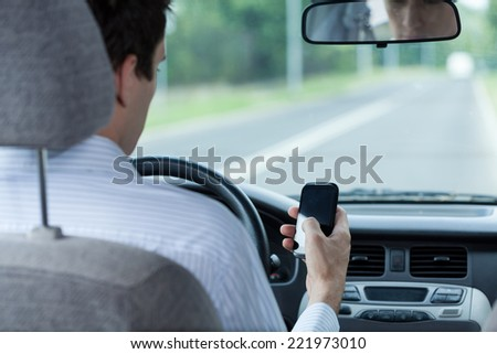 Man using phone while driving a car - stock photo