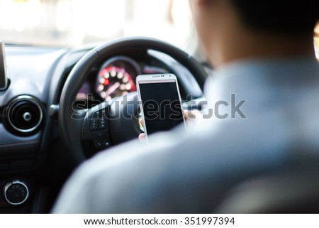 man using phone while driving the car (selective focus) - transportation and vehicle concept - stock photo