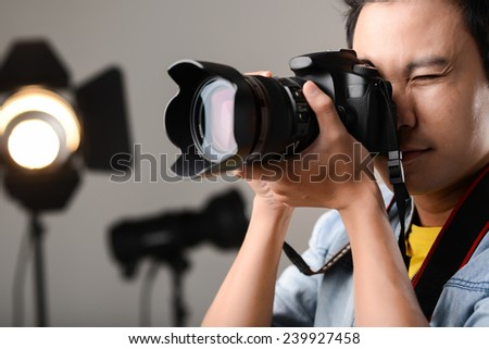 Man using professional camera in the studio - stock photo