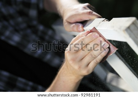 man using sandpaper on an old window frame