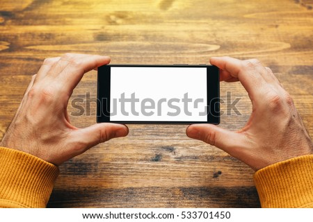 Man using smart phone in horizontal landscape orientation for streaming movies or browsing picture gallery, blank screen as copy space