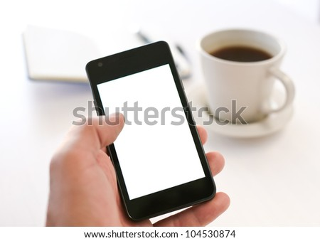Man using smartphone, close-up, coffee and planning book on the background