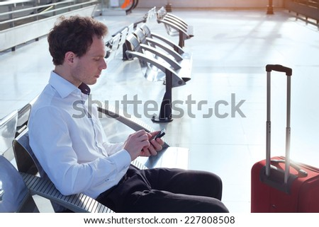 man using smartphone in the airport - stock photo